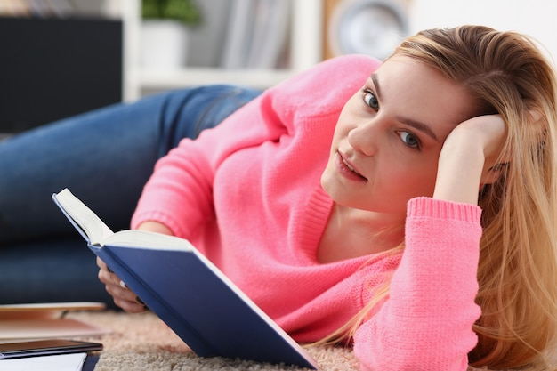 Młoda blond kobieta leży na podłodze czytać książkę