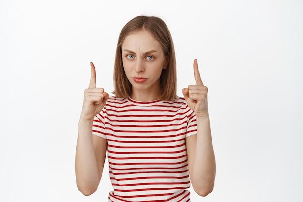 Młoda blond kobieta marszczy brwi i krzywi się, wskazując palcami na coś podejrzanego, wyraża wątpliwości i niechęć, nie zgadza się, stojąc nad białą ścianą.