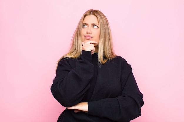 Młoda blond kobieta myśli, czując się niepewnie i zdezorientowana, z różnymi opcjami, zastanawiając się, którą decyzję podjąć przeciwko płaskiej ścianie