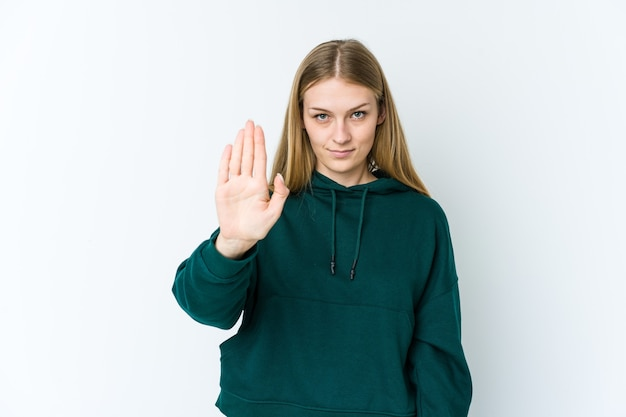 Młoda blond kobieta na białym stojącym z wyciągniętą ręką pokazano znak stopu na białym tle, uniemożliwiając ci.