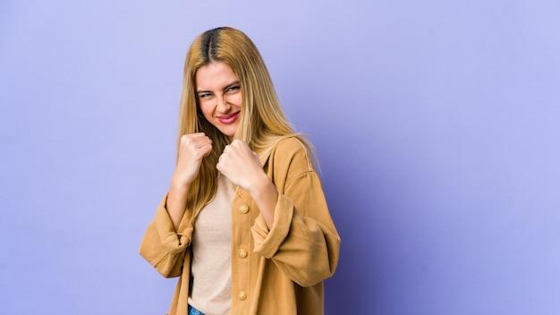 Młoda blond kobieta na białym tle na fioletowym tle pokazuje pięść do kamery, agresywny wyraz twarzy.