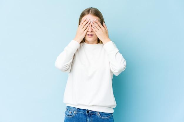 Młoda blond kobieta na białym tle na niebieskiej ścianie boi się obejmujących oczy rękami.