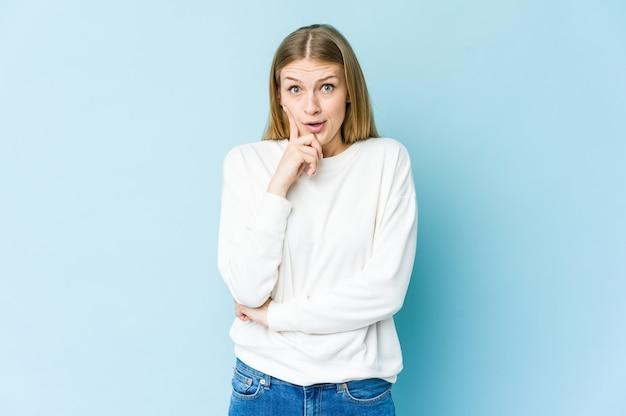 Młoda blond kobieta na białym tle na niebieskiej ścianie mając jakiś świetny pomysł, pojęcie kreatywności