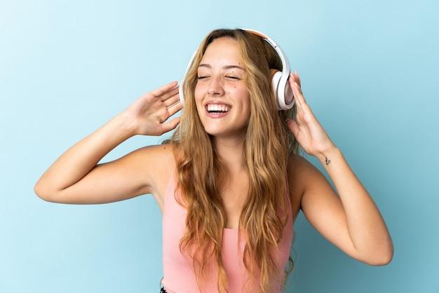 Młoda blond kobieta na białym tle na niebieskiej ścianie słuchania muzyki i śpiewu