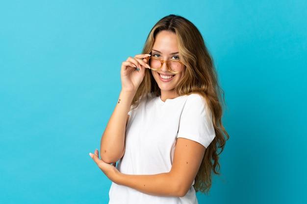 Młoda blond kobieta na białym tle na niebieskiej ścianie w okularach i szczęśliwa