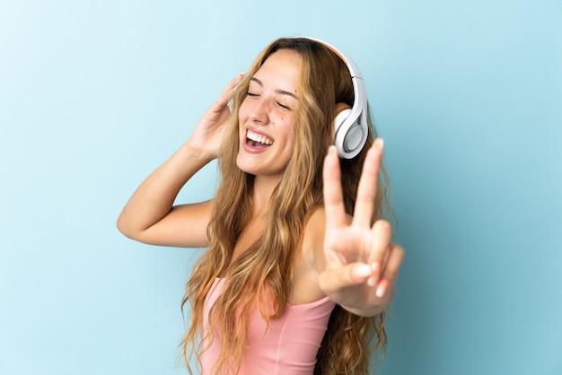 Młoda blond kobieta na niebieskim tle słuchania muzyki i śpiewu