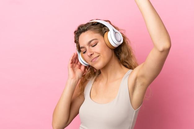 Młoda blond kobieta na różowym tle słucha muzyki i tańczy
