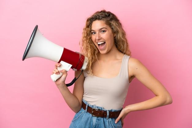 Młoda blond kobieta na różowym tle trzymająca megafon i uśmiechnięta