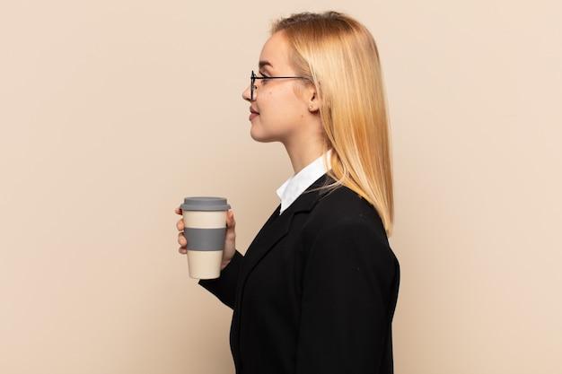 Młoda blond kobieta na widoku profilu, chcąc skopiować przestrzeń do przodu.