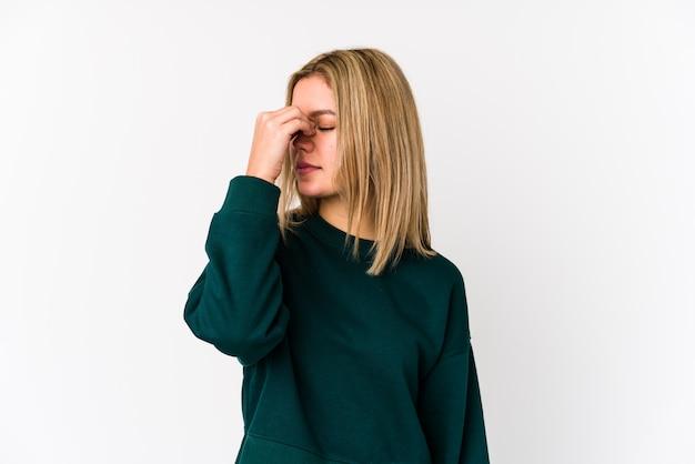 Młoda blond kobieta o ból głowy, dotykając przodu twarzy
