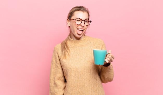 Młoda blond kobieta o pogodnym, beztroskim, buntowniczym nastawieniu, żartuje i wystawia język, dobrze się bawi. koncepcja kawy