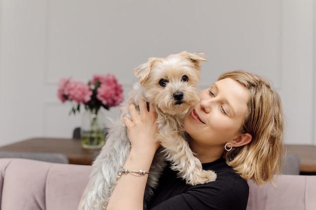 Młoda blond kobieta obejmuje psa yorkshire terrier siedząc na różowej kanapie w przytulnym, nowoczesnym salonie właściciel i zwierzę mają ten sam kolor włosów uroda i zdrowie pielęgnacja psów