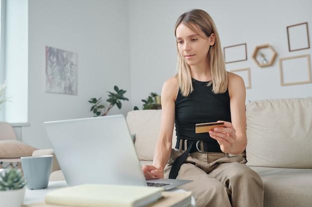 Młoda blond kobieta patrząca na wyświetlacz laptopa podczas surfowania w sklepie internetowym i wybierania nowych ubrań lub gadżetów i płacenia kartą kredytową