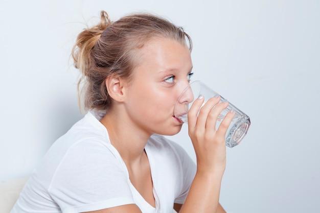 Młoda blond kobieta pije czystą wodę przestrzega reżimu picia. koncepcja opieki zdrowotnej.