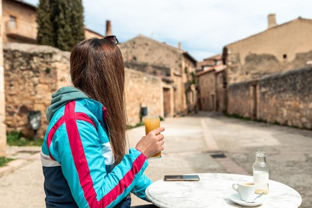 Młoda blond kobieta pije sok na tarasie baru w starym hiszpańskim mieście.