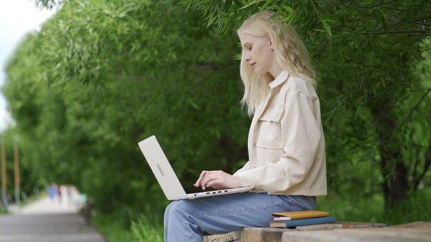 Młoda blond kobieta pracuje na laptopie w parku. praca na odległość. ciepły letni dzień na świeżym powietrzu. 4k uhd