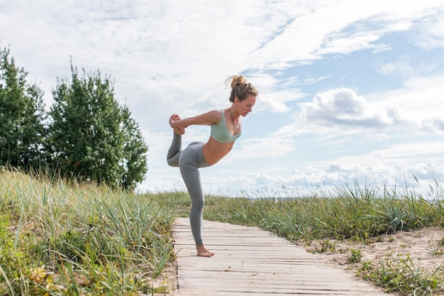 Młoda blond kobieta praktykuje jogę na plaży. profesjonalny trener wykonuje ćwiczenia rozciągające na drewnianej ścieżce nad morzem.
