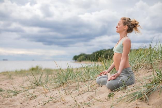 Młoda blond kobieta praktykuje jogę na wybrzeżu. profesjonalny trener medytujący na nadmorskiej wydmie.