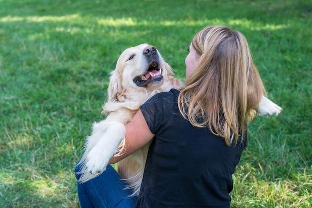 Młoda blond kobieta przytula psa. pies rasy retriever z dziewczyną w parku.