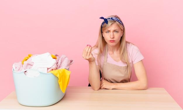 Młoda blond kobieta robi gest capice lub pieniądze, mówiąc, aby zapłacić. koncepcja prania ubrań
