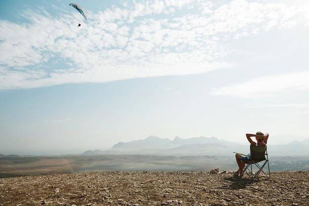 Młoda blond kobieta siedzi na szczycie wzgórza
