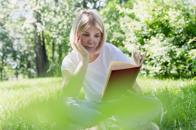 Młoda blond kobieta siedzi na trawie w parku w słoneczny letni dzień i czyta książkę. rekreacja i kształcenie na odległość w przyrodzie.