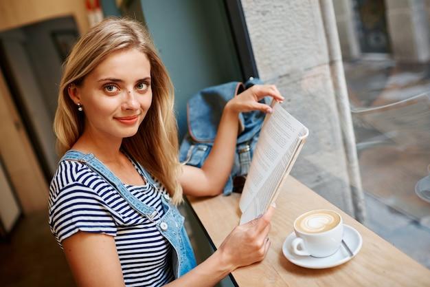 Młoda blond kobieta siedzi w kawiarni i czyta
