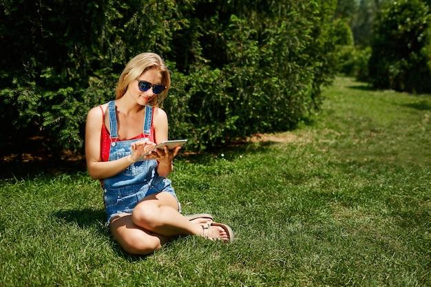 Młoda blond kobieta siedzi w parku i za pomocą tabletu