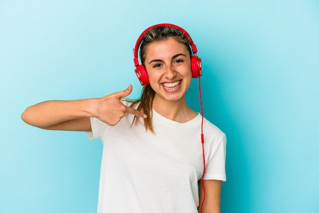 Młoda blond kobieta słuchanie muzyki w słuchawkach na białym tle na niebieskim tle osoba wskazująca ręką na przestrzeni kopii koszuli, dumny i pewny siebie
