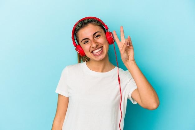 Młoda blond kobieta słuchanie muzyki w słuchawkach na białym tle na niebieskim tle pokazuje numer dwa palcami.