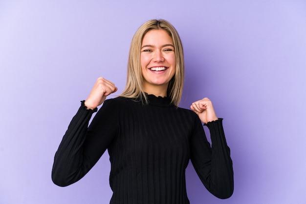 Młoda blond kobieta świętuje zwycięstwo, pasję i entuzjazm, szczęśliwy wyraz
