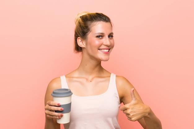 Młoda blond kobieta trzyma kawę na wynos z kciukami do góry, ponieważ stało się coś dobrego