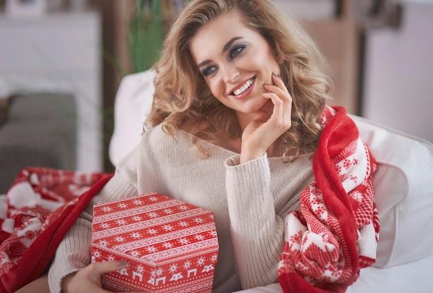 Młoda blond kobieta trzyma prezent gwiazdkowy