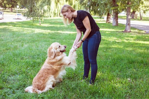Młoda blond kobieta trzyma psa za przednie łapy. pies rasy retriever z zabawą z dziewczyną w parku