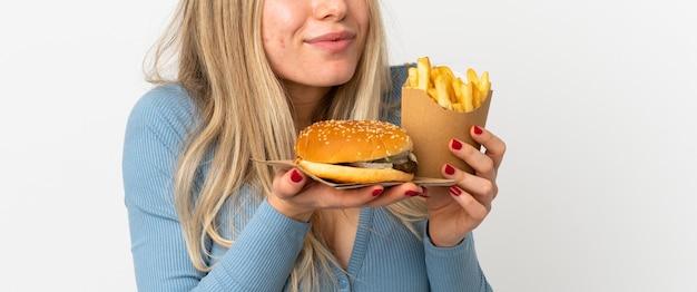 Młoda blond kobieta trzyma smażone frytki i cheeseburgera na białym tle