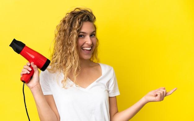 Młoda blond kobieta trzyma suszarkę do włosów odizolowaną na żółtym tle wskazując palcem w bok