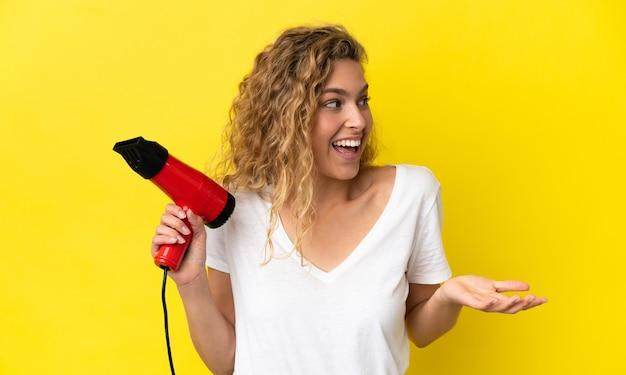 Młoda blond kobieta trzyma suszarkę do włosów odizolowaną na żółtym tle z wyrazem zaskoczenia, patrząc w bok