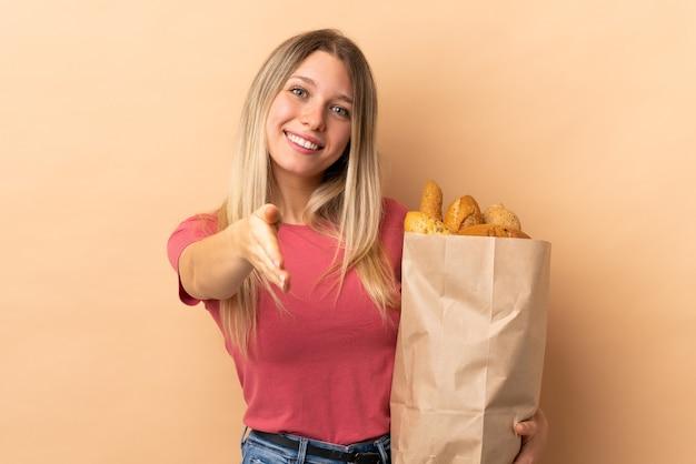 Młoda blond kobieta trzyma torbę pełną pieczywa na białym tle na uzgadnianie ściany beżowej po dobrej cenie