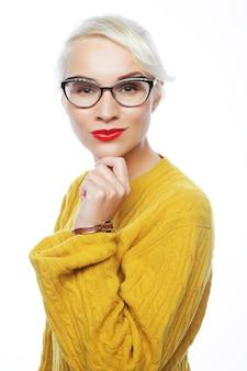 Młoda blond kobieta ubrana w żółty sweter na białym tle