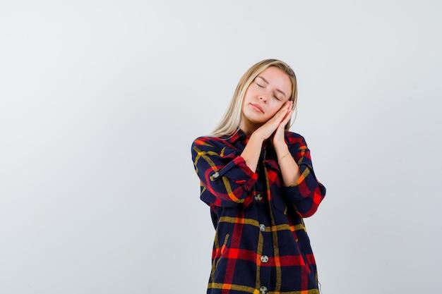 Młoda blond kobieta udaje, że śpi