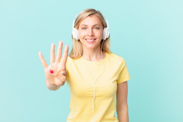 Młoda blond kobieta uśmiecha się i wygląda przyjaźnie, pokazując numer cztery i słuchając muzyki.