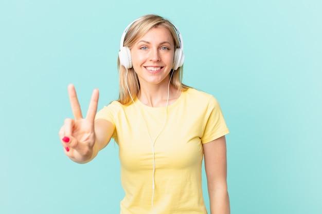Młoda blond kobieta uśmiecha się i wygląda przyjaźnie, pokazując numer dwa i słuchając muzyki.