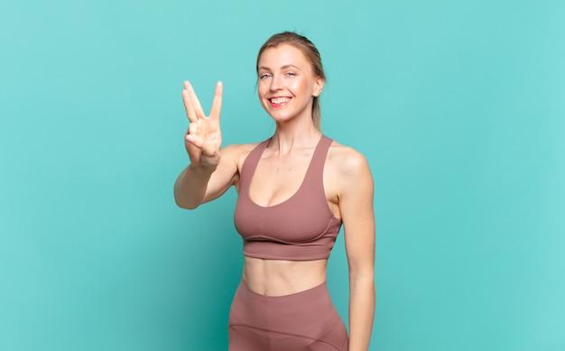 Młoda blond kobieta uśmiecha się i wygląda przyjaźnie, pokazując numer trzy lub trzeci z ręką do przodu, odliczając. koncepcja sportu