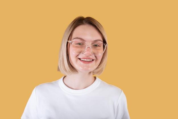 Młoda blond kobieta uśmiecha się odizolowana na żółto
