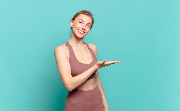 Młoda blond kobieta uśmiecha się radośnie, czuje się szczęśliwa i pokazuje koncepcję w przestrzeni kopii z dłonią. koncepcja sportu