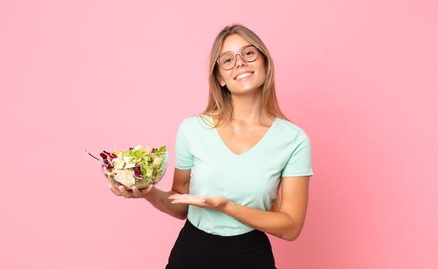 Młoda blond kobieta uśmiecha się radośnie, czuje się szczęśliwa, pokazuje koncepcję i trzyma sałatkę