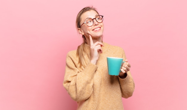 Młoda blond kobieta uśmiecha się radośnie i marzy lub wątpi, patrząc w bok. koncepcja kawy