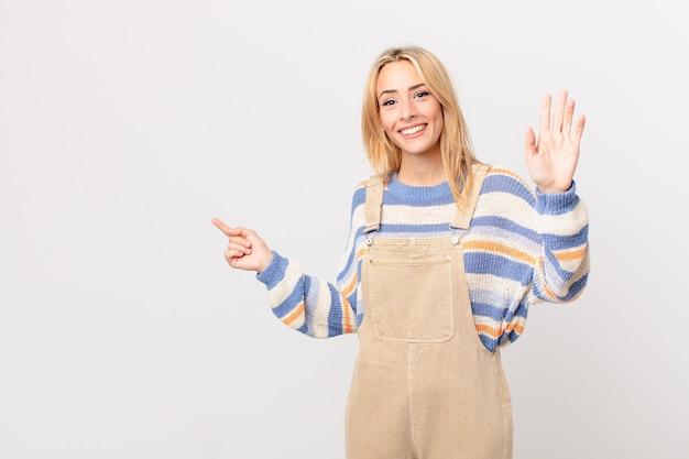 Młoda blond kobieta uśmiecha się radośnie, machając ręką, witając cię i pozdrawiając