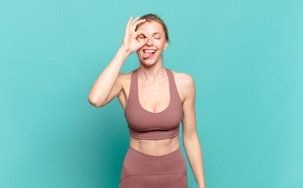 Młoda blond kobieta uśmiecha się radośnie ze śmieszną miną, żartując i patrząc przez wizjer, szpiegując sekrety. koncepcja sportu