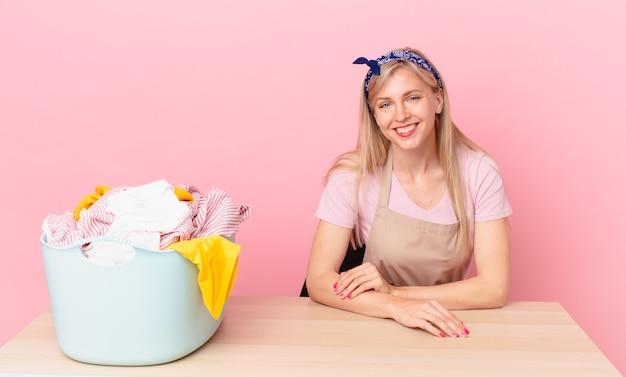 Młoda blond kobieta uśmiecha się szczęśliwie z ręką na biodrze i pewnie. koncepcja prania ubrań